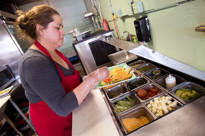 Co-owner Josie Payan sprinkles cheese on an order at Benny's Tacos in Longmont.  For more photos go to www.dailycamera.com (Autumn Parry/Staff Photographer) May 18, 2016