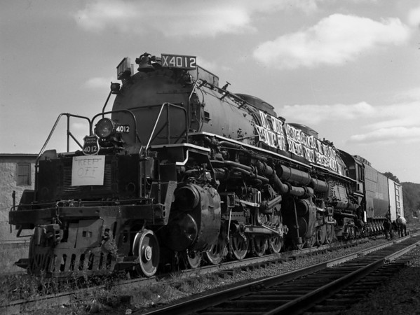 """UP Big Boy 4012 - Greenfield, MA (?) in transit to Steamtown, Bellows Falls, VT. Banner reads """"I'm the largest loco in the world going to Steamtown, Bellows Falls VT"""".  TAA-ST-011-1_K"""