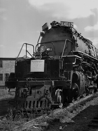 """UP Big Boy 4012 - Greenfield, MA (?) in transit to Steamtown, Bellows Falls, VT. Banner reads """"I'm the largest loco in the world going to Steamtown, Bellows Falls VT"""".  TAA-ST-011-4_K"""