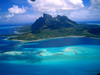 Bora Bora from the sky. An amazing mountainous island surrounded by reef and a bright blue lagoon.