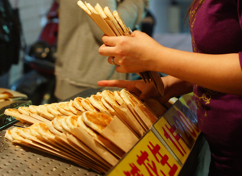 This is a travel photo of some delicious street food (Taiwanese hot cakes) being sold at the bustling Shilin night market in the heart of Taipei, Taiwan.