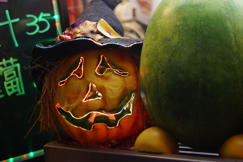 Today's daily travel photo is of a Halloween pumpkin brightly illuminated and adorned with decorations at a stall in the Shilin Night located in Taipei, Taiwan.