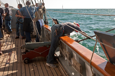 """Crew member of the tall ship """"Californian"""" cleaning one of the guns during battle re-enactment sail."""