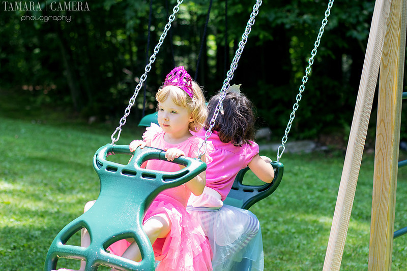 a picture of two young girls on a swing set at a birthday party