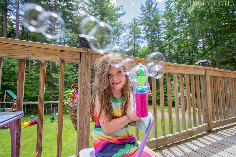 a picture of a young girl blowing bubbles at a camera