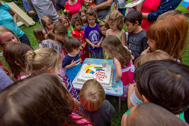 a picture of children around a cake at a birthday party