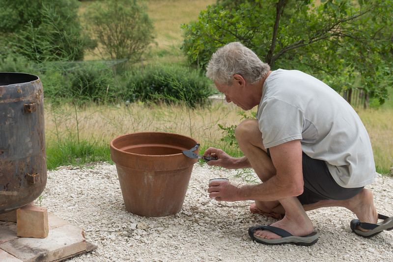 Use refractory cement to stick the pot upside down in the metal shell.