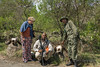 Guide and tourist examining buffalo skulls with a ranger 4, Arusha NP, Tanzania