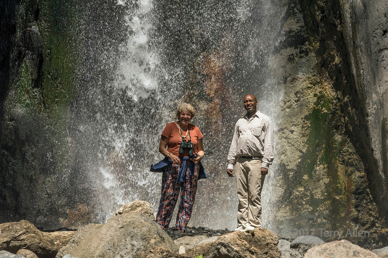 Guide and client enjoying the cool breeze from Maio Falls, Jekukumia River, Arusha National Park, Tanzania