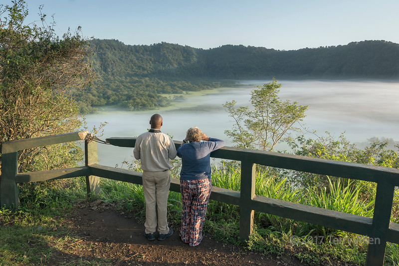 Guide and tourist at Ngurdoto Crater overlook with morning mist, Arusha NP, Tanzania