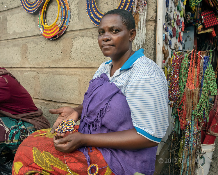 Portrait of a woman showing her beading at the Maasai Market, central Arusha, Tanzania