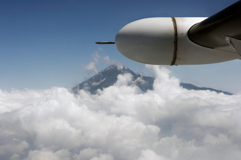 Small plane flying past Mount Meru with snow near peak, near Arusha, Tanzania, East Africa