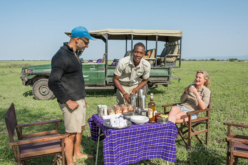 Phabian preparing lunch on the savanna, Grumeti Game Reserve, Serengeti, Tanzania