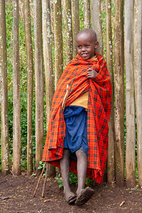 Young Maasai boy leaning against a fence
