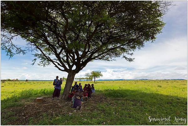It was a very beautiful-sky-day with mountain ranges in the background, perfectly fine weather. We saw a huge Acacia in the distance as we slowly approached them, a teacher in mangosteen shade carrying a child on her hip. Young kids, a future of the tribe, paid full attention to her.