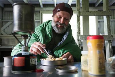 A tramper eats breakfast in Parawai Hut, Tararua Range, Tararua Forest Park