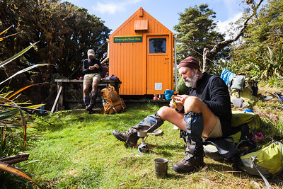 Two trampers eat lunch outside Dracophyllum Hut, Tararua Forest Park