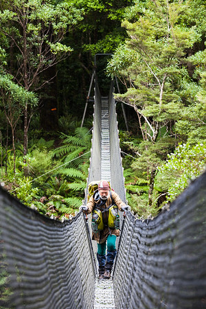 Male Te Araroa tramper crossing swingbridge, Otaki  River, Tararua Forest Park