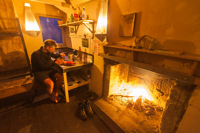 A male tramper eats alone with the fire burning inside Mid Waiohine Hut, Waiohine River, Tararua Forest Park, North Island