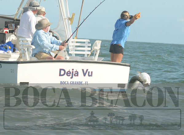 A handler releases a tarpon on the Deja Vu boat during the tarpon tournament on Boca Grande.