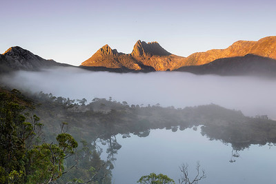 Cradle mountain is a famous recreation area.  Often shrouded in clouds it was a delight to catch it at sunrise above the fog over the lake and forest