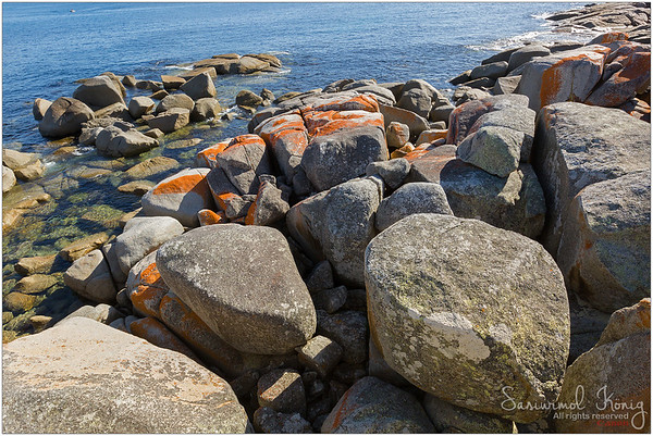 Huge boulders with red lichen on them.. A contrast between red and green. Love the crystal clear water