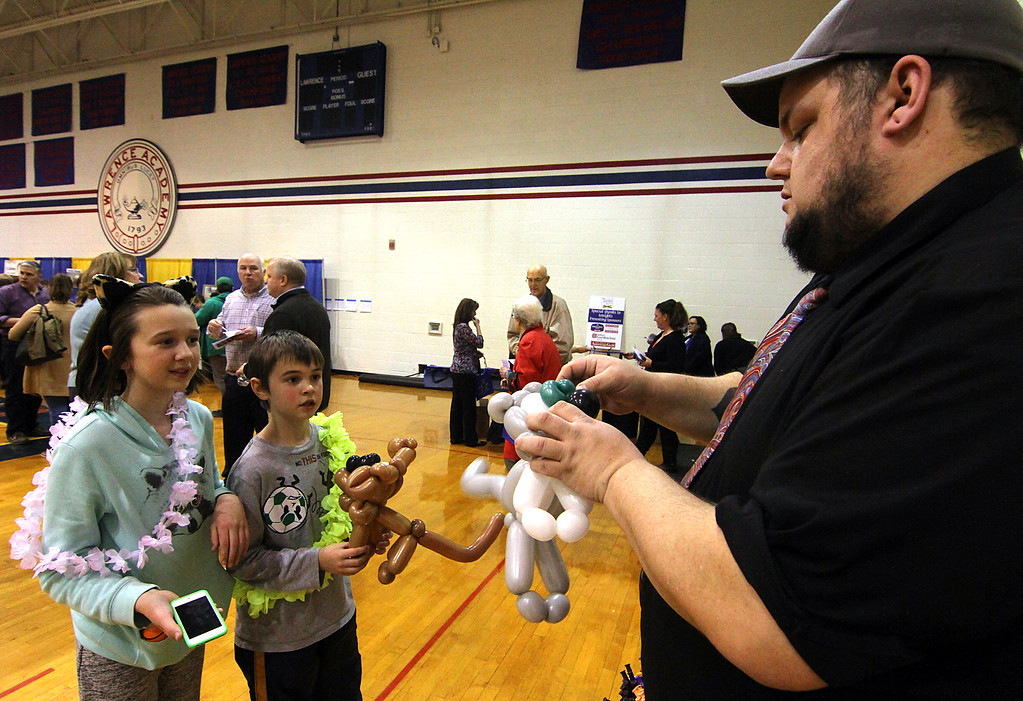 . Local kids, Faith Coleman,11, and her brother Aaron Coleman,9, both of Groton, watch Dan Staples of Dan\'s Balloon\'s, make a balloon cat for them at the Taste of the Town event held at Lawrence Academy in Groton.Nashoba Valley Voice Photo bt David H. Brow.