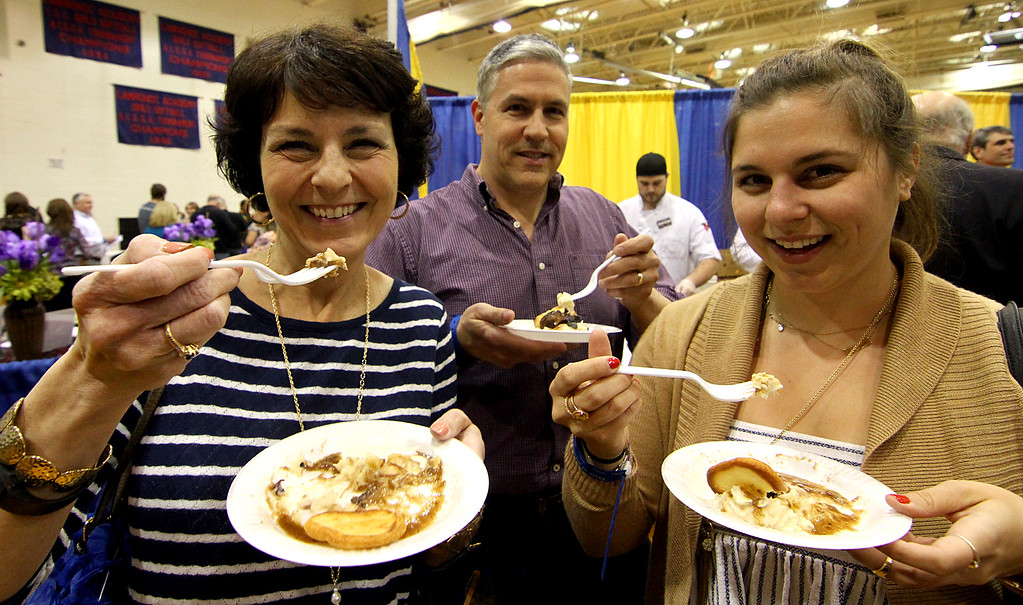 . Groton residents, L-R, Diane D\'Innocenzo, Frank D\'Innocenzo and their daughter Ashley D\'Inncenzo, sample some of the many food offered at the annual Taste of the Town event. Nashoba Valley Voice Photo bt David H. Brow