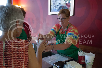 Pam Dillon and Kerry Dillon serve food during the Taste of the Ville in Manhattan, KS, on June 10, 2017. The event, which included 14 of the restaurants in the Aggieville Buisness District, was a fundraiser for the Philanthropic Educational Organization's scholarships. (Justin Wright | Collegian Media)