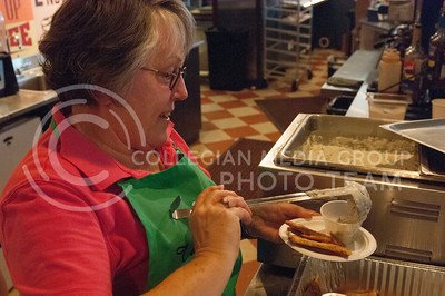 Carol Mattox serves food during the Taste of the Ville in Manhattan, KS, on June 10, 2017.The event, which included 14 of the restaurants in the Aggieville Buisness District, was a fundraiser for the Philanthropic Educational Organization's scholarships. (Justin Wright | Collegian Media)