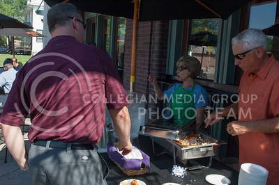 Kevin Bahner and Liz Bahner serve food during the Taste of the Ville in Manhattan, KS, on June 10, 2017.The event, which included 14 of the restaurants in the Aggieville Buisness District, was a fundraiser for the Philanthropic Educational Organization's scholarships. (Justin Wright | Collegian Media)