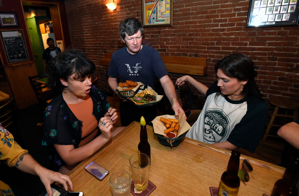 . Fred Nicolai brings a food order to Chancey Hawthorne, left, and Abby Murphy at the Pearl Street Pub on Thursday in Boulder. For more photos of activity at a couple tavern licenses go to dailycamera.com Jeremy Papasso/ Staff Photographer 08/02/2018