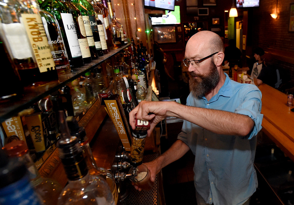 . Bartender David Wood pours a draft beer for a customer at the Pearl Street Pub on Thursday in Boulder. For more photos of activity at a couple tavern licenses go to dailycamera.com Jeremy Papasso/ Staff Photographer 08/02/2018