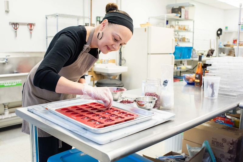 KELLY FLETCHER, REFORMER CORRESPONDENT -- Dar Tavernier-Singer, Co-Founder and Creative Director of Tavernier Chocolates, decorates Heart Mendiants (solid dark chocolate with rose petals, raspberry and sea salt).  All of Tavernier's chocolates are handmade in Brattleboro with locally sourced ingredients and ethically sourced chocolate.