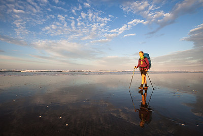 Female tramper (40's) walks Te Araroa Trail in early morning, Ninety Mile Beach/Te Oneroa-a-Tōhē, Northland
