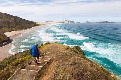 Female tramper (40's) walks Te Araroa Trail. Werahi Beach and Cape Maria van Diemen in background