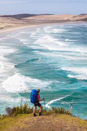 Female tramper (40's) standing above breaking surf. Werahi Beach and Cape Maria van Diemen in background