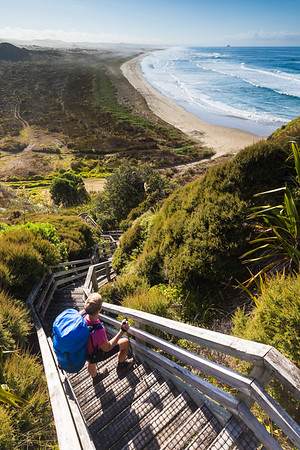 Female tramper (40's) descends stairs on Te Araroa Trail on Scott Point, overlooking Ninety Mile Beach, Northland