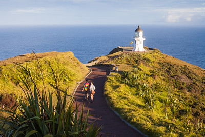 Man and woman (20's) walk on pathway leading to Cape Reinga lighthouse and Pacific Ocean