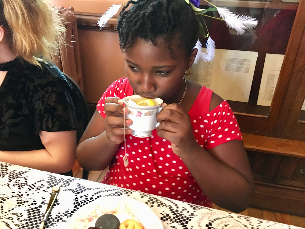 . Helene Carter, 10, of Tyngsboro delicately sipped tea at the Billerica Historical Society\'s event. Photo by Mary Leach