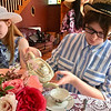 Kayla Lavoie pours a cup of tea while Caitlin Salter prepares a plate of treats. Photo by Mary Leach