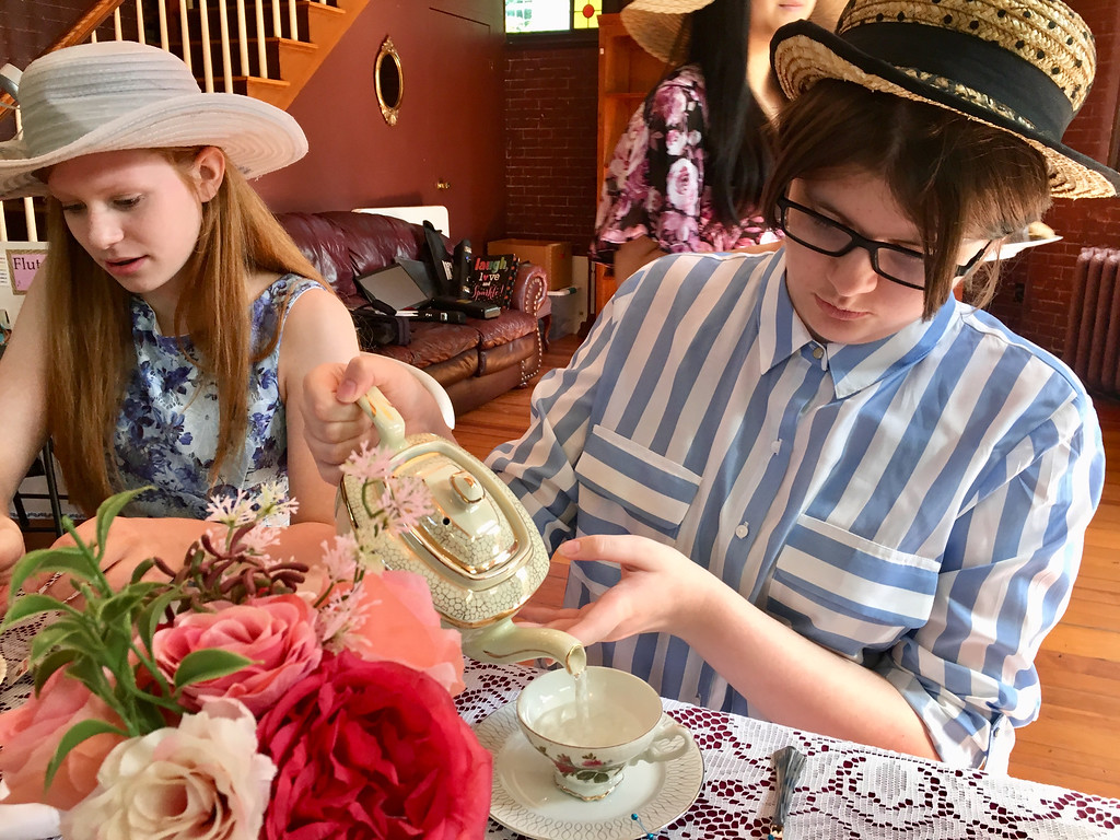 . Kayla Lavoie pours a cup of tea while Caitlin Salter prepares a plate of treats. Photo by Mary Leach