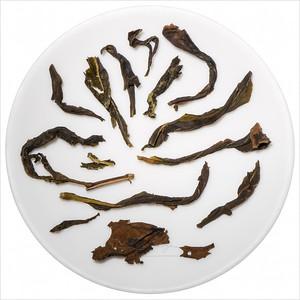 Shui Hsien - Duch vody. Infused oolong tea leaves on porcelain. Vyluhované čajové lístky v porcelánové násypce.