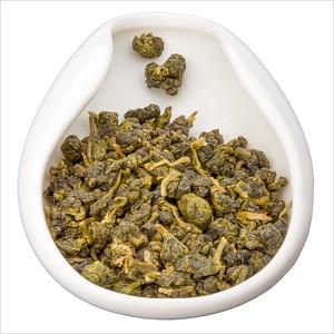 Tai Wan Cui Yu Wu Long - Nefritový oolong. Tea leaves in porcelain hopper. Čajové lístky v porcelánové násypce.