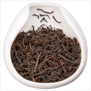 Ceylon OP - vysokohorský Ceylon OP. Black tea leaves in porcelain hopper. Čajové lístky černého čaje v porcelánové násypce.