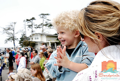 Two year old Drew Clayton Miller claps to the music, held by his mother Caryn Hall.