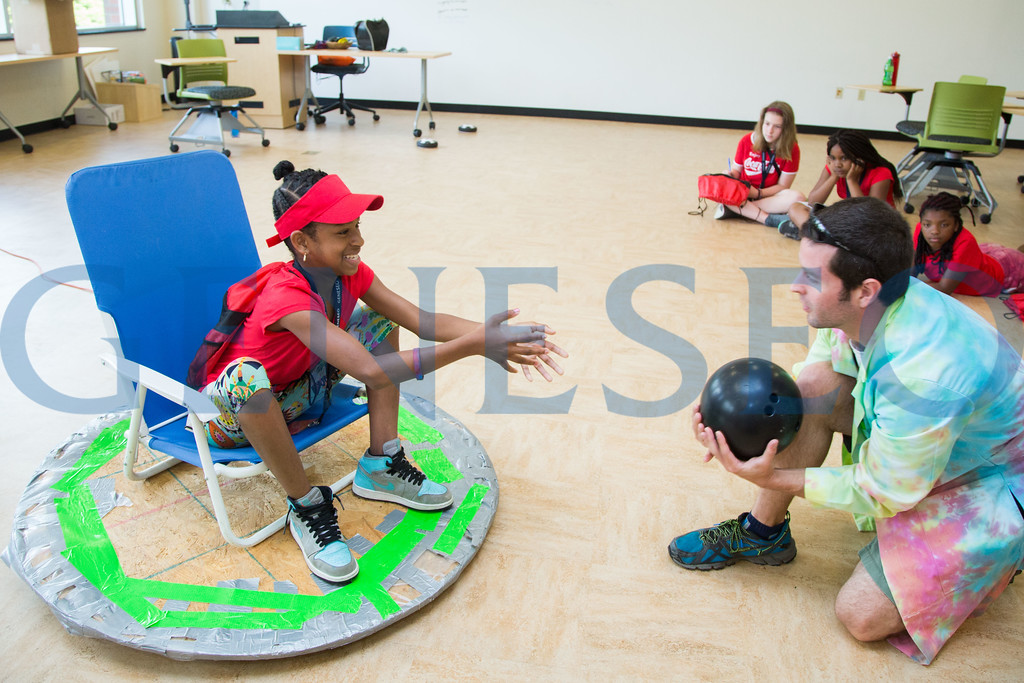 Dan Dalmat, a teacher from Honeoye Central School District, works with Koshara Leonard on a custom hoverboard to demonstrate Newton's three laws of motion.
