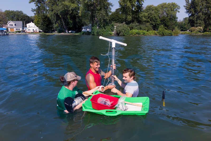 Left to right: Jacalyn M. Wittmer Malinowski, assistant professor of geology, Jake Okun '19 and Gavin Gleasman '19 extract core samples from Conesus Lake in an effort to determine how the ecosystem has changed and responded to anthropogenic influences over the years. / Photo by Keith Walters '11