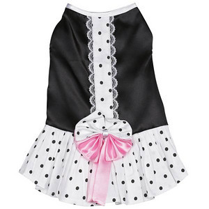 Cocktail Party Dress features a soft, luxurious, black satin bodice with white satin trim on the neck and armholes. The flouncy polka dot skirt is topped with a half-dotted, half-begonia pink bow at the waist to pull the look together. A sweet polka dot stripe with lace trim runs down the back.
