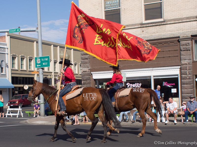 """The beggining of the Round-up parade with flags carrying the banner and the slogan """"Let'er Buck"""".<br /> <br /> It couldn't have been more perfect weather.  It's about 10am, 80 degrees and sunny."""
